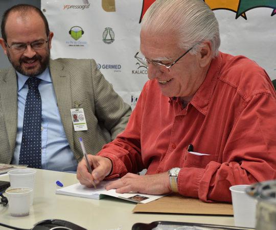 """Prof. Dr. Luiz Jorge Fagundes, Coordenador Científico do CEADS, no momento em que autografava seu Livro """"Sempre com Elas"""" ao Prof. Dr. Marcelo Menta Nico, Coordenador do Fórum de debates sobre """"Estomatologia""""."""