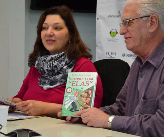 """Dra. Roberta Fachini Jardim Criado, Coordenadora do Fórum de Debates sobre """"Reações Medicamentosas e Urticária"""", recebendo das mãos do Prof. Dr. Luiz Jorge Fagundes, Coordenador Científico do CEADS, o exemplar do Livro """"Sempre com Elas""""."""