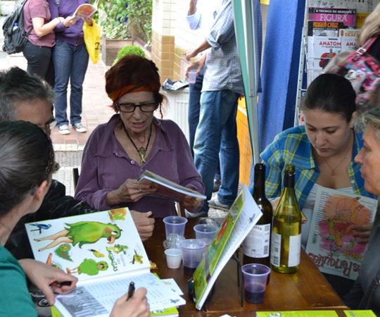 """A Ilustradora Mariza Dias Costa, uma das mais antigas do Grupo das Periquitas, sentada à cabeceira da mesa e Crau da Ilha, a primeira da direita para a Esquerda, autora do Projeto, durante a sessão de Autógrafos do Livro sobre o Projeto """"As Periquitas""""."""