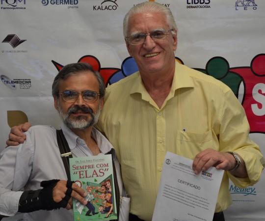 """Prof. Dr. Raymundo Azevedo, Colaborador do CEADS de posse do Livro """"Sempre com Elas"""" e o Prof. Dr. Luiz Jorge Fagundes, Coordenador Científico do CEADS de posse do Certificado de Palestrante do 40 Fórum de Debates sobre """"Pesquisa Clínica"""",pertencente ao Prof. Dr. Raymundo Azevedo."""