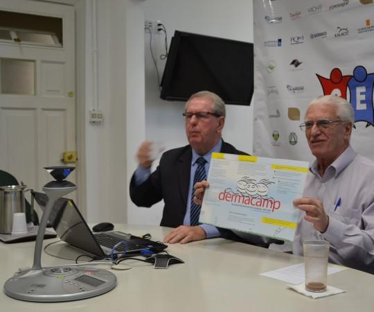 """O Prof. Dr. Luiz Jorge Fagundes,Coordenador Científico do CEADS, exibindo o Folder do Primeiro """"DERMACAMP"""",realizado em 2001 e o Prof. Mande lbaum, Organizador do DERMACAMP e Coordenador do Fórum de Debates."""