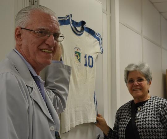 """A Sra. Maria do Carmo Haramura, Esposa do Prof. Fabio e o Prof. Dr. Luiz Jorge Fagundes, diante da Sala Prof. Fabio Haramura, cuja placa estava envolta pela Camisa da Seleção do """"CEDOM"""""""