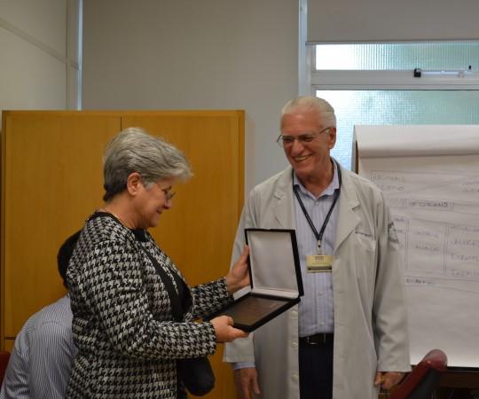 A Sra. Maria do Carmo Haramura, com a Placa em Homenagem ao Prf. Fabio Haramura, ofertada pelo CEADS por meio de seu Coordenador Científico o Prof. Dr. Luiz Jorge Fagundes.