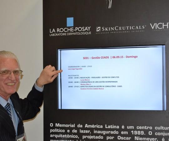 """O Prof. Dr. Luiz Jorge Fagundes, Coordenador Científico do CEADS, diante do Painel indicativo do Curso """"Gestão do CEADS"""", durante o 70 Congresso Braileiro de Dermatologia."""