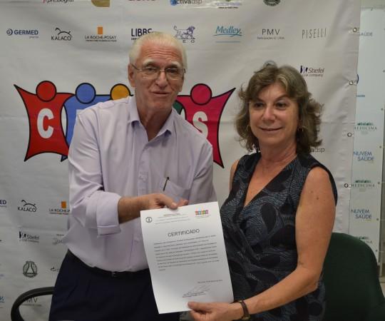 A Sra. Frida Strum, Representante da Drogaderma e o Prof. dr. Luiz Jorge Fagundes,Coordenador Científico do CEADS, durante a entrega do Certificado de Patrocinadora Exclusiva  da Drogaderma  no 51 Fórum de Debates.