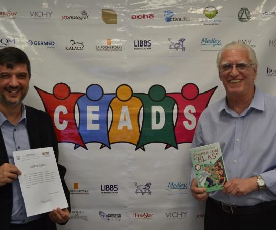 """O Prof. Dr. Marcelo Arnone com seu Certificado de Coordenador do 54 Fórum de Debates e o Prof. Dr. Luiz Jorge Fagundes, Coordenador Científico do CEADS com seu Livro """"Sempre com Elas""""."""