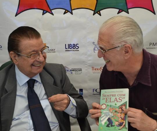 """O Prof. Dr. Luiz Carlos Cucé, recebe das mãos do Prof. Dr. Luiz Jorge Fagundes, um exemplar do Livro """"Sempre com Elas"""" de autoria do Prof. Fagundes."""