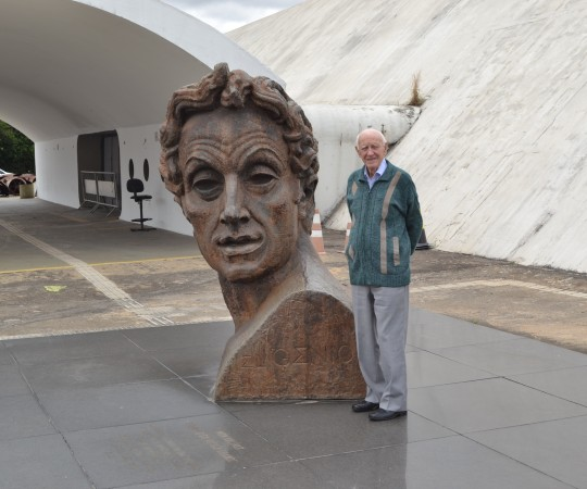 "O Sr Juca Fagundes, Colaborador do CEADS, junto à Escultura presente na entrada do ""Memorial da América Latina""."