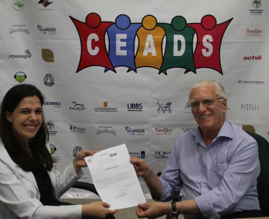 O Prof. Dr. Luiz Jorge Fagundes, Coordenador Científico do CEADS, no momento da entrega do Certificado de Coordenadora do 61 Fórum de Debates à Dra. Mariana Hafner.