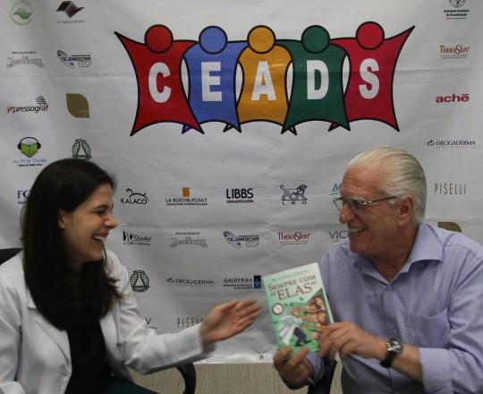 """A Dra. Mariana Hafner, Coordenadora do 61 Fórum de Debates do CEADS, no momento em que recebe das mãos do Prof. Dr. Luiz Jorge Fagundes, o Livro """"Sempre Com Elas""""."""