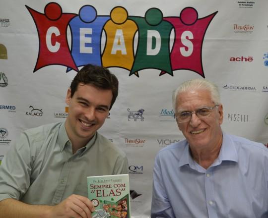 """O Dr. João Avancini, Colaborador do CEADS, recebe do Prof. Dr. Luiz Jorge Fagundes, Coordenador Científico do CEADS, o exemplar do Livro: """"Sempre com Elas"""" de autoria do Prof. Dr. Fagundes."""