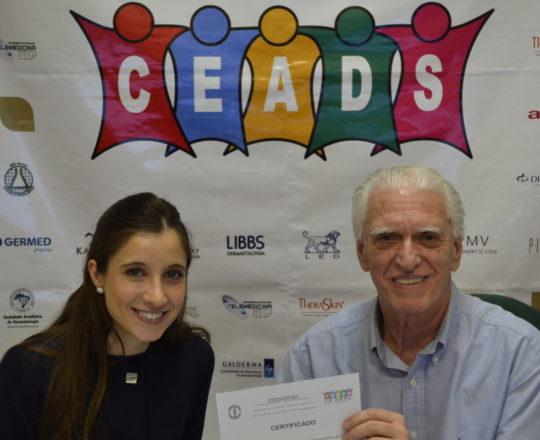 A Dra. Nathalia Targa, Colaboradora do CEADS e Coordenadora do Fórum, recebe das mãos do Prof. Dr. Luiz Jorge Fagundes, o Certificado de Palestrante do Fórum sobre Criocirugia.