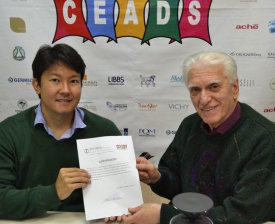 O Dr. Denis Miyashiro, recebe das mãos do Prof. Dr. Luiz Jorge Fagundes, Coordenador Científico do CEADS, o Certificado de Palestrante do 67 Fórum de Debates.