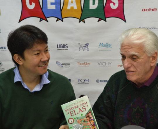 """O Prof. Dr. Luiz Jorge Fagundes, Coordenador Científico do CEADS, entrega ao Dr. Denis Miyashiro, o seu Livro """"Sempre com Elas"""", durante o 67 Fórum de Debates do CEADS."""