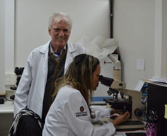 O Prof. Dr. Luiz Jorge Fagundes, Coordenador Científico do CEADS e a Biomédica Fátima Morais, Colaboradora do CEADS, durante a apresentação das lâminas de DST, pertencentes ao acervo do CEADS.