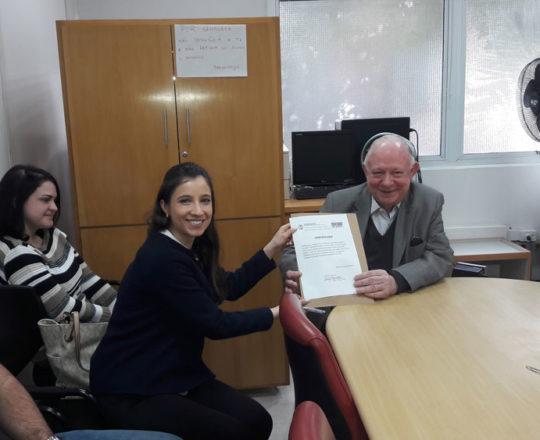 A Dra. Nathalia Targa Pinto, entrega o Certificado de Palestrante ao Prof. Dr. Sidnei Martini.
