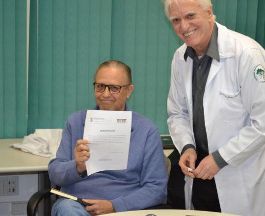 """O Prof. Wesley Wey Jr, Coordenador de Gestão do CEADS, recebe das mãos do Prof. Dr. Luiz Jorge Fagundes, Coordenador Científico do CEADS, o Certificado de Palestrante do Tema: """"Consequências de uma Gestão Despreparada""""."""