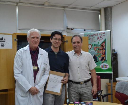 """O Prof. Gustavo Haramura, recebe das mãos do Prof. Dr. Fagundes, Coordenador Científico do CEADS e do Dr. Armando Pinto de Souza, o Certificado de Palestrante do tema: """"Fundamentos de Gestão""""."""