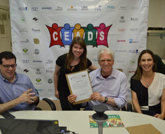 O Prof. Fagundes, junto com o Prof. Beni Grimblat, entregam à Sra. Jeany Bentel, o Certificado de Patrocinador Exclusivo ao Laboratório La Roche Posay.