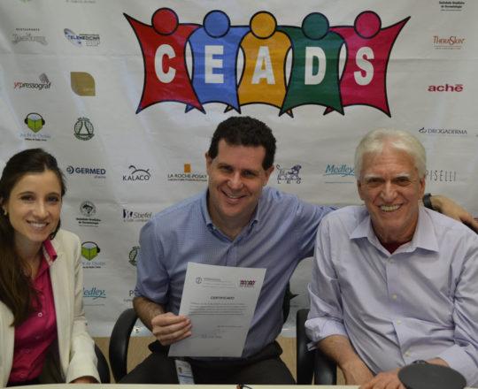 O Prof. Beni Grimblat, recebe das mãos do Prof.Dr. Luiz Jorge Fagundes e da Dra. Nathalia Targa, o Certificado de palestrante do 69 Fórum de debataes do CEADS.