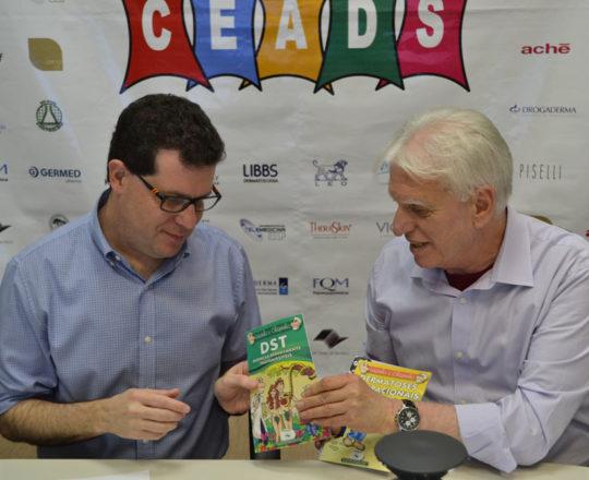 O Prof. Beni Grimblat, recebe as Histórias em quadrinhos do CEADS das mãos do Prof. Fagundes.