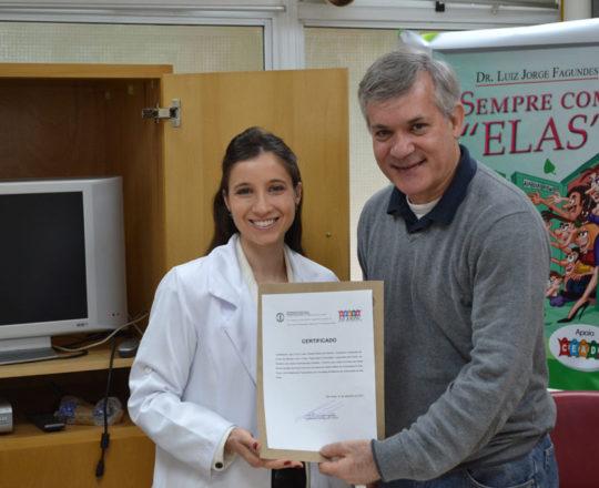 A Dra. Nathalia Targa Pinto, Colaboradora do CEADS, no momento da entrega do Certificado de Participação do Prof. Lucas Blanco, Tesoureiro do CEADS, nos cursos  sobre Fundamentos da Gestão,promovidos pelo Centro de Estudos e de Apoio à Dermatologia Sanitária.