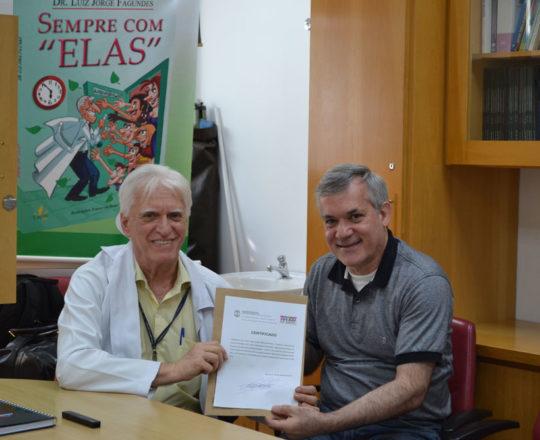 """O Prof. Dr. Luiz Jorge Fagundes, Coordenador Científico do CEADS, entrega ao Prof. Lucas Blanco, Tesoureiro do CEADS, o Certificado de Palestrante do Curso sobre """"Fundamentos da Gestão."""