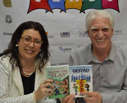 """A Profa. Dra. Raquel Leão Orfali, de posse dos Livros """"Sempre com Elas"""". sobre DST e """"Ninguém realiza o que desconhece"""", sobre Gestão, de autoria do Prof. Dr. Luiz Jorge Fagundes, Coordenador Científico do CEADS."""