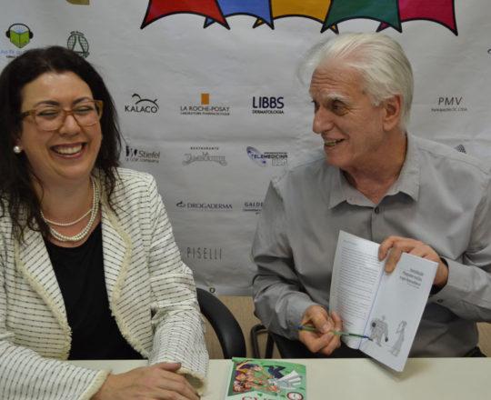 """O Prof. Fagundes, mostra à Profa. Dra. Raquel Leão Orfali, alguns faros humorísticos do Livro sobre """"Gestão."""