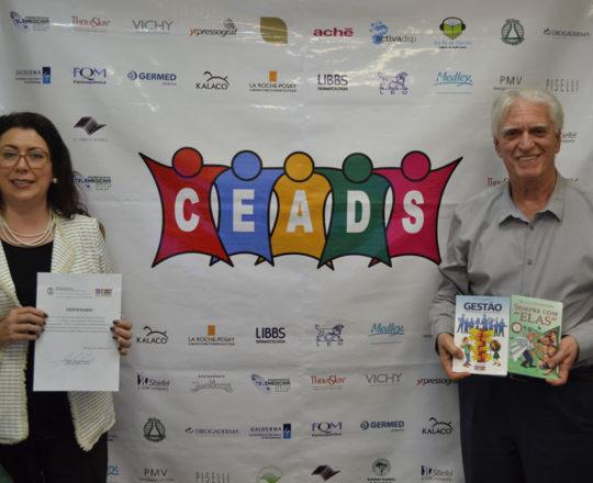 """O Prof. Dr. Luiz Jorge Fagundes mostra seus dois livros: """"Sempre com Elas"""" e Ninguém realiza o que Desconhece"""" , enquanto a Profa. Dra. Raqul Leão Orfali, mostra seu Certificado de Palestrante."""