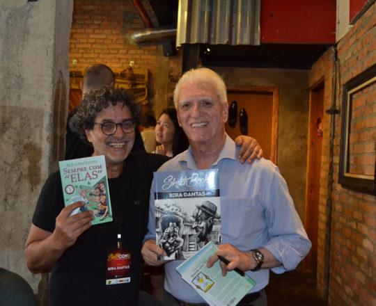 """O Artista Plástico Bira Dantas, Colaborador do CEADS, com o exemplar do Livro """"Sempre com Elas"""", de autoria do Prof. Dr. Luiz Jorge Fagundes, que está com o exemplar do Livro de Lançamento do artista Bira."""