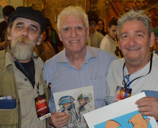 O Prof. Dr. Luiz Jorge Fagundes, ao lado dos artistas colaboradores do CEADS, João Zero, a esquerda do Prof. Fagundes e do Artista Minighitti, ambos expondo seus exemplares de lançamento.