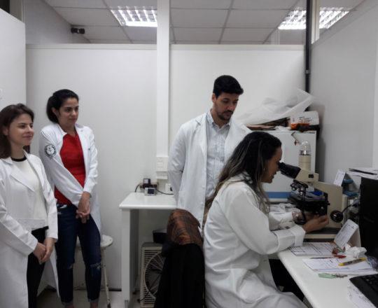 A Biomédica Fátima Morais, Colaboradora do CEADS e os Estagiários de DST de novembro de 2017 durante a exposição de lâminas do acervo do CEADS.