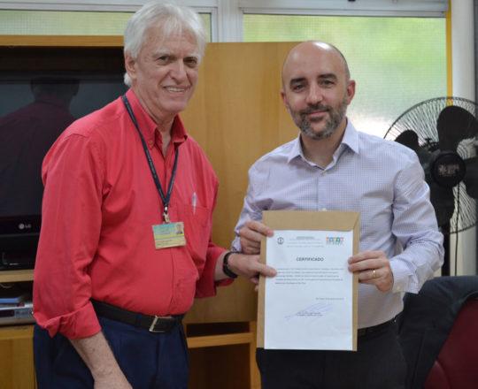 """O Prof. Gustavo Ferreira, recebe das mãos do Prof. Dr. Luiz Jorge Fagundes, o Certificado de Palestrante do tema: """"Aspectos Jurídicos da Responsabilidade Médica""""."""