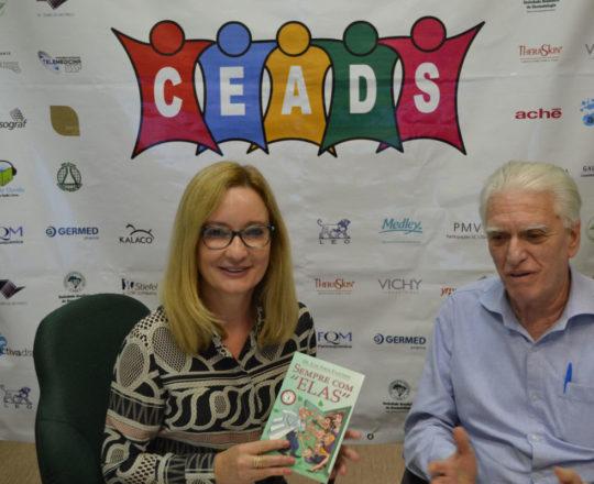 """A Dra. Ana Paula Meski, recebe das mãos do Prof. Dr. Luiz Jorge Fagundes. um exemplar do Livro """"Sempre com Elas"""", de autoria do Prof. Fagundes."""