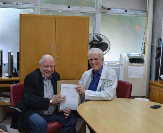 O Prof. Dr. Luiz Jorge Fagundes, Coordenador Científico do CEADS, no momento da entrega do Certificado de palestrante ao Prof. Dr. José Sidnei Colombo Martini.