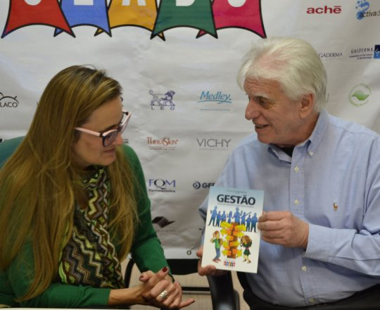 """O Prof. Dr. Luiz Jorge Fagundes, entrega à Dra. Ana Cristina o Livro sobre Gestão: """" Ninguém Realiza o que Desconhece"""", elaborado pela Equipe de Gestores do CEADS."""