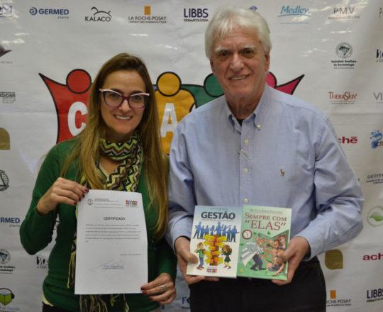 O Prof. Dr. Fagundes, exibe os livros elaborados pelo CEADS e o Certificado de Palestrante de posse da Dra. Ana Cristina.