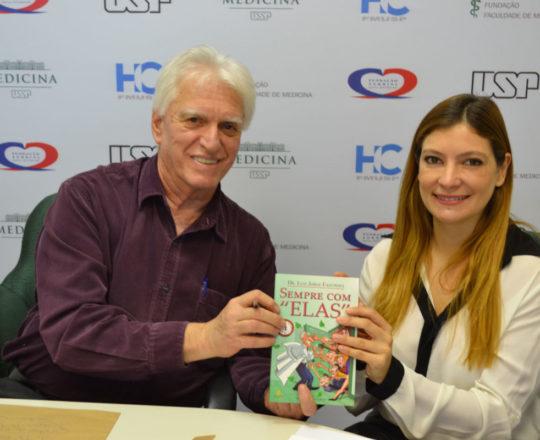 """A Dra. Ana Maria Corbett, recebe das mãos do Prof. Dr. Luiz Jorge Fagundes, um exemplar do Livro """"Sempre com Elas"""" de autoria do Prof. Dr. Fagundes."""