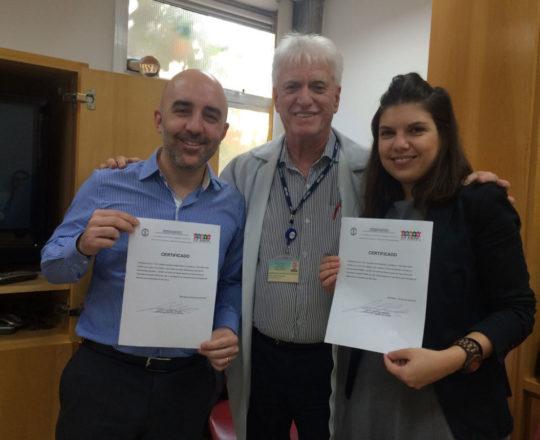 O Prof. Dr. Luiz Jorge Fagundes entrega ao Dr. Gustavo Ferreira e à Dra. Fernanda Mello Machado os Certificados de Palestrantes.