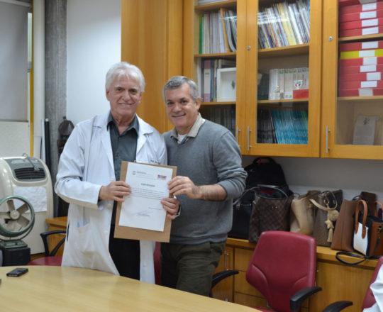 O Prof. Dr. Luiz Jorge Fagundes concede ao Prof. Lucas Blanco o Certificado de Palestrantre.
