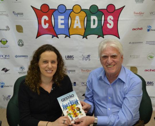"""O Prof. Dr. Fagundes entrega à Profa. Dra. Anita Rotter o Livro sobre """"Fundamentos da Gestão"""", elaborado pela Equipe do CEADS."""