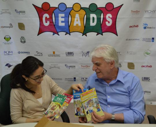 """O Prof. Dr. Fagundes faz a entrega das """"Histórias em Quadrinhos""""com temas de Dermatologia Sanitária."""