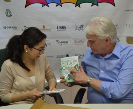 """O Prof. Dr. Fagundes entrega o Livro """"Sempre com Elas"""" de sua autoria à Dra. Alessandra Anzai."""