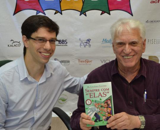 """O Dr. Caio Lamunier recebe das mãos do Prof. Dr. Fagundes, o livro """"Sempre com Elas"""" de autoria do Prof. Dr. Luiz Jorge Fagundes."""