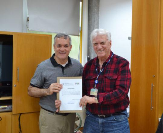 O Prof. Dr. Fagundes faz a entrega do Certificado de Palestrante ao Prof. Lucas Blanco.