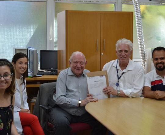 O Prof. Dr. Fagundes entrega o Certificado de Palestrante ao Prof. Dr. Sidnei Martini, junto à Dra. Nathalia Targa, ao Pianista Luciano Ruas e às Estagiárias de DST.